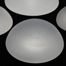 silicone breast implants with micro textured surface isolated on black background